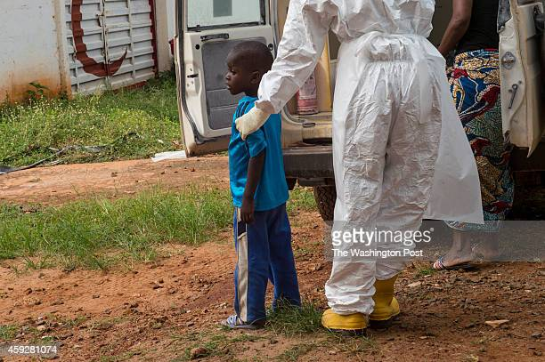 Mamie Kuyateh helps a 4yearold boy off an ambulance at a holding center in in Freetown Sierra Leone on Tuesday November 18 2014 Ebola cases are...