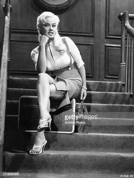 Mamie Van Doren sitting on the stairs in a scene from the film 'Girls Town' 1959