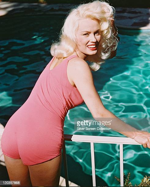 Mamie Van Doren, US actress and singer, wearing a pink swimsuit, leaning on a handrail overlooking a swimming pool, circa 1955.