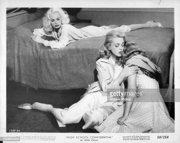 Mamie Van Doren watches Jan Sterling from bed as she comforts another girl in a scene from the film 'High School Confidential' 1958