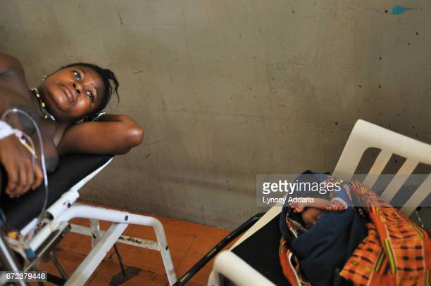 Mamma Sessay lies on the delivery table next to her firstborn twin as she waits to deliver the second at the Magburaka Government Hospital in Sierra...