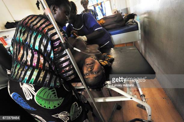 Mamma Sessay screams in pain and with fear on the delivery table as she is comforted by her sister Amenata left a nurse as she prepares to deliver...
