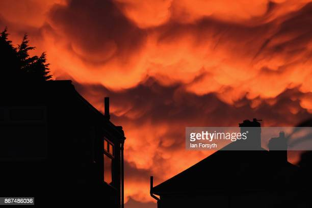 Mammatus clouds form over houses at sunset on October 28 2017 in SaltburnbytheSea England Mammatus means mammary cloud and they are a cellular...