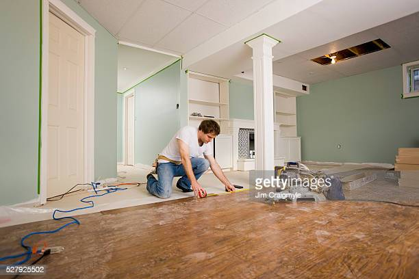 man 30's installing hardwood laminate flooring in a basement - renovation stock pictures, royalty-free photos & images