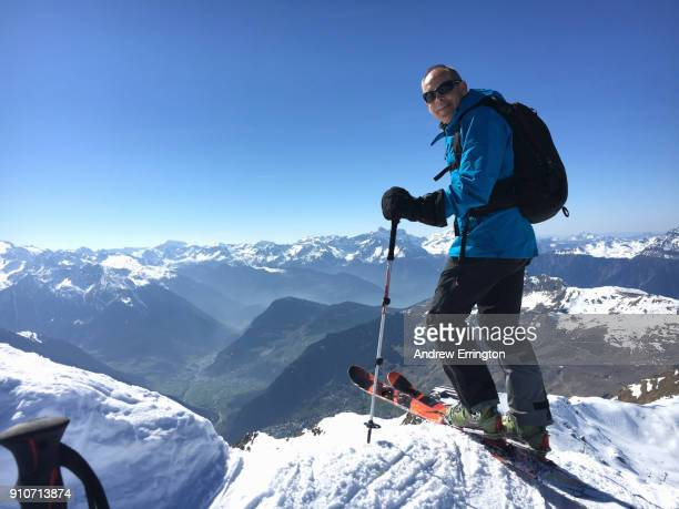 Man 55-60years old, on telemark skis, smiling, looking to camera with view of Swiss Alps behind