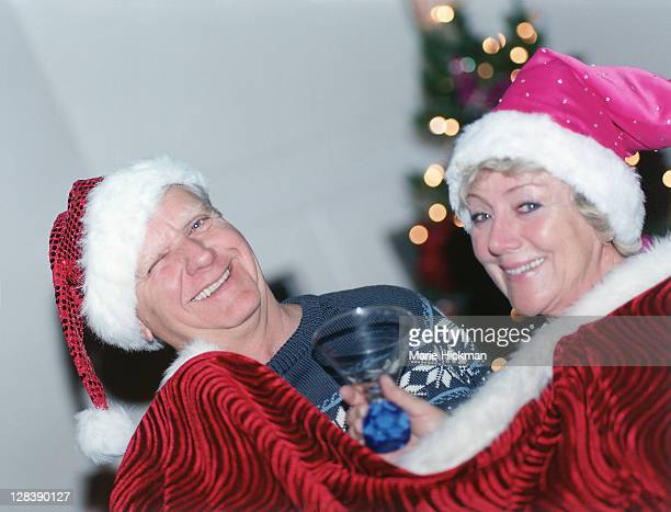 Man, 64 years old, and woman 60 years old in a red cape with Santa hats with martini glass