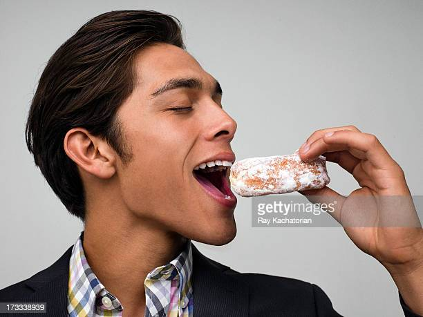 Man about to bite a donut