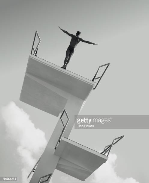 Man about to dive from diving board backward (B&W)