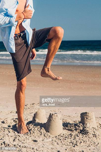 Man About To Stomp On Sand Castle