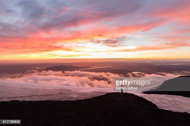 Man above the clouds on mountain Iceland vulcan sunset