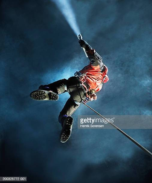 man abseiling in cave, holding torch, view from below - spelunking stock pictures, royalty-free photos & images
