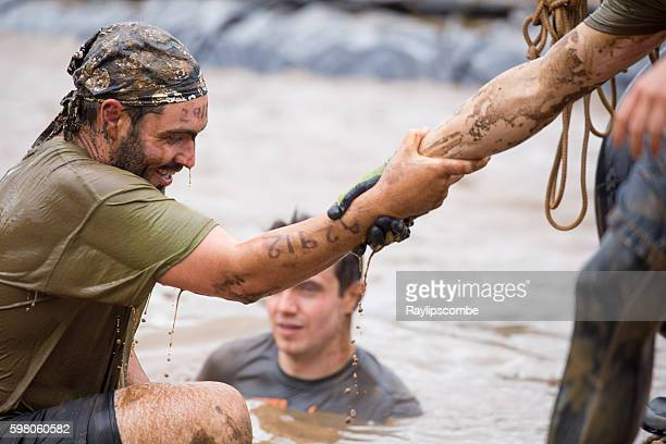 Man accepts a helping hand out of some muddy water
