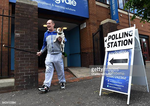 A man accompanied by his dog laughs as he exits a polling station after voting in the EU referendum on June 23 2016 in Belfast Northern Ireland The...