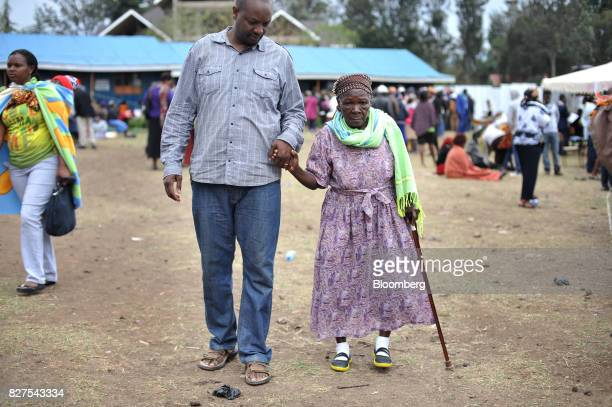 A man accompanies his elderly mother to vote in a polling station at the Don Bosco center in Kiserian Kenya on Tuesday Aug 8 2017 The politicians are...