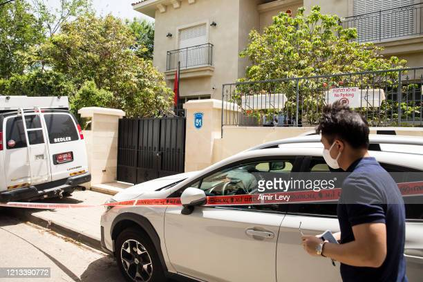 Man accompanies police officers and forensic teams as they enter the house of China's Ambassador to Israel Du Wei, after he was found dead in his...