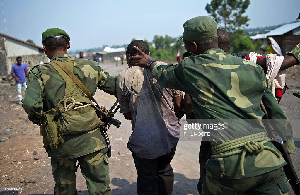 A man accused by the Congolese Army of being a spy of rebels of the M23 movement is tied and taken away on July 16, 2013 in Munigi on the outskirts of Goma in the east of the Democratic Republic of the Congo. The army in the Democratic Republic of Congo on July 16 pursued an offensive against rebels of the M23 movement to protect the North Kivu provincial capital of Goma. M23, a movement launched by Tutsi defectors from the army who accuse the Kinshasa government of reneging on a 2009 peace deal, last year occupied Goma for 10 days before pulling out under international pressure.