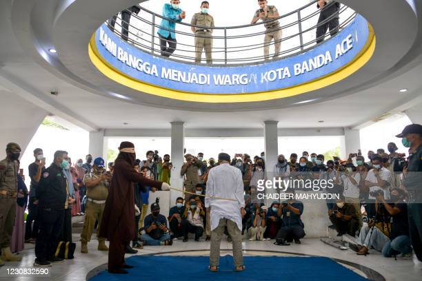 Man accused of having gay sex is publicly caned by a member of the Sharia police in Banda Aceh on January 28, 2021. - Aceh is the only region in the...
