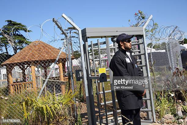 A man acting as a security guard stands outside the UNHCR 'Border Control Garden' during the press preview day of the Hampton Court Palace Flower...