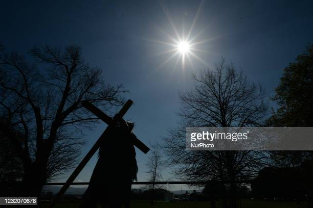Man acting as Jesus and carrying a cross seen during a Solemn Procession on Good Friday 2021, walking and praying from the General Post Office to the...