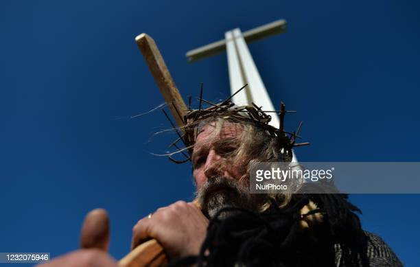 Man acting as Jesus, carrying a cross, during a Solemn Procession on Good Friday 2021 from the General Post Office to the 'Papal Cross' in Dublin's...