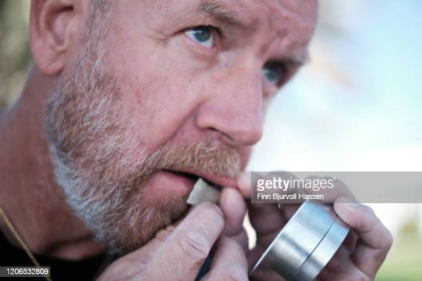 man adding a portion of snuff, snus smokeless tobacco under lip - finn bjurvoll stock pictures, royalty-free photos & images