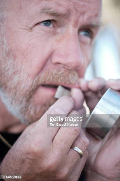 man adding a portion of snuff, snus smokeless tobacco under lip - finn bjurvoll - fotografias e filmes do acervo