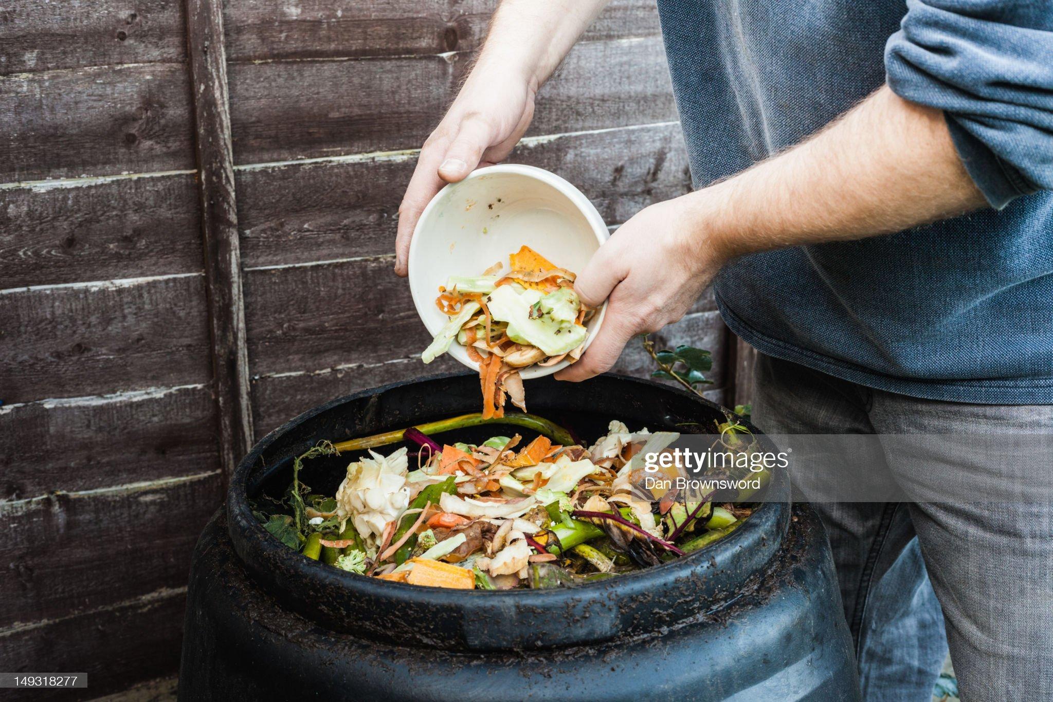Stock Photo : homme ajoutant du compost dans une poubelle