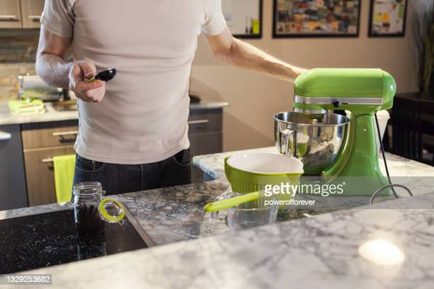 man adding vanilla extract while baking chocolate chip cookies - measuring spoon stock pictures, royalty-free photos & images