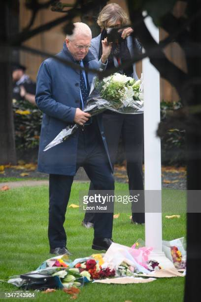 Man adds a bunch of flowers to floral tributes laid within the grounds of the Houses of Parliament on October 18, 2021 in London, England. Sir David...