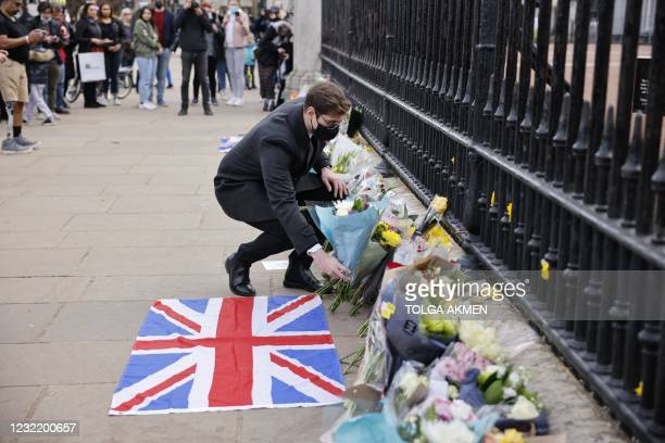 Man adds a bunch of flowers to the tributes laid at the railings at the front of Buckingham Palace in central London on April 9, 2021 after the...