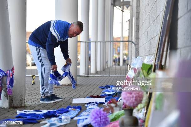 A man adds a Leicester City scarf to floral tributes lined up outside Leicester City Football Club's King Power Stadium in Leicester eastern England...
