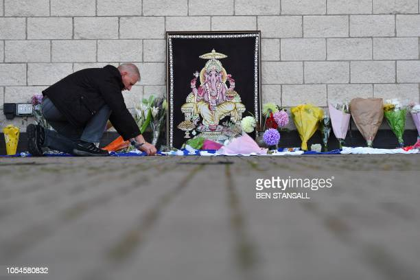 TOPSHOT A man adds to flowers and Leicester City scarfs left as tributes outside Leicester City Football Club's King Power Stadium in Leicester...