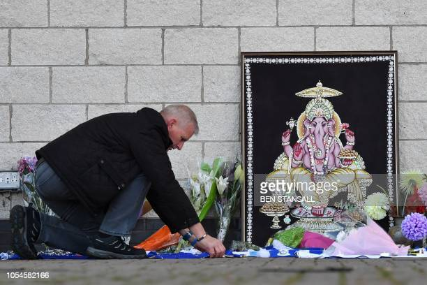 A man adds to flowers and Leicester City scarfs left as tributes outside Leicester City Football Club's King Power Stadium in Leicester eastern...