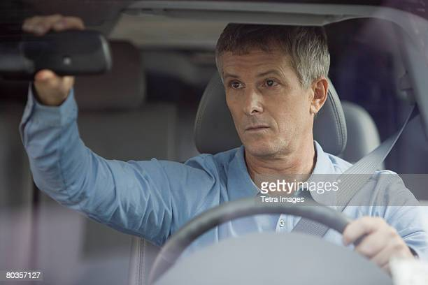 Man adjusting car rear view mirror