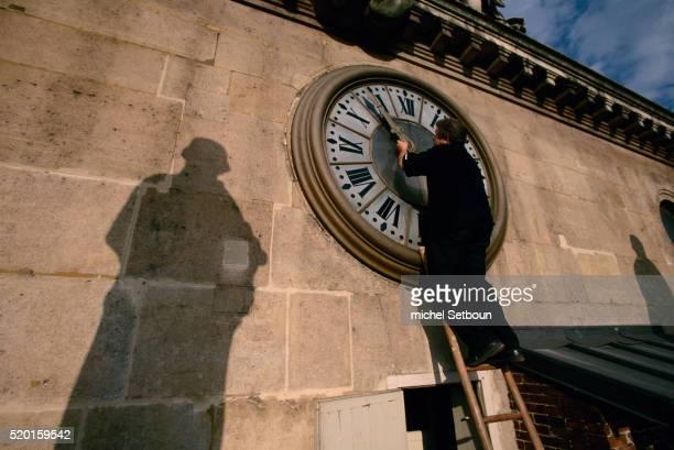 Man Adjusting Clock at Palais de Justice