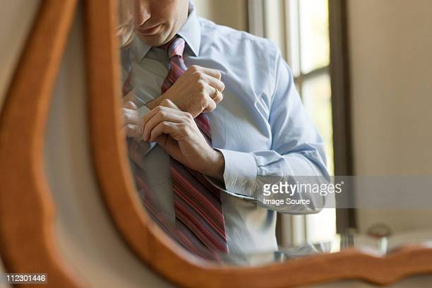 Man adjusting cuffs in mirror