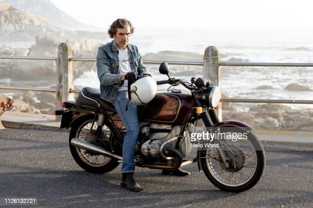 man adjusting helmut on vintage motorcycle - motorcycle stock pictures, royalty-free photos & images