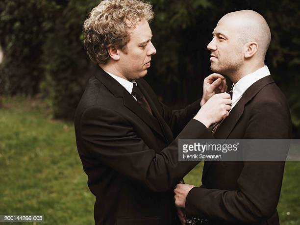 Man adjusting male friend's tie, outdoors, side view