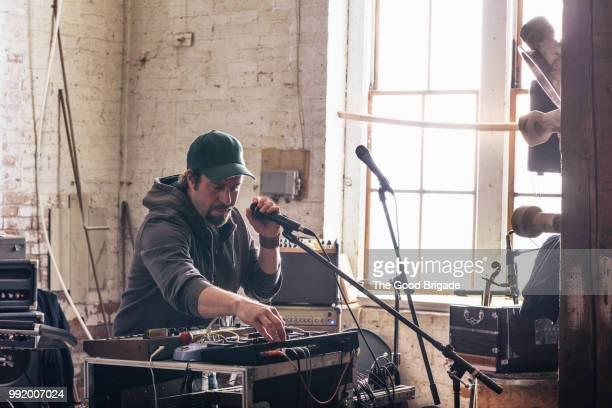 Man Adjusting Sound Mixer in Recording Studio