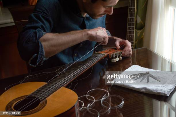 man adjusting strings in guitar on table at home - adjusting stock pictures, royalty-free photos & images