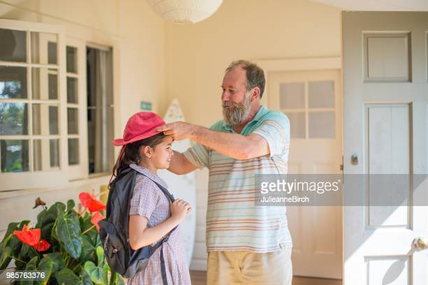 man adjusting sun hat on granddaughter at home - australasia stock pictures, royalty-free photos & images