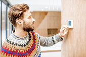 Man adjusting temperature with thermostat at home