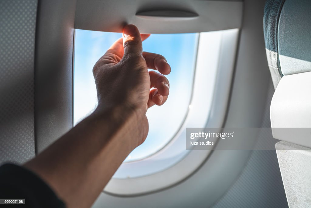 Man Adjusting the Blinds on an Airplane Window POV : Stock Photo