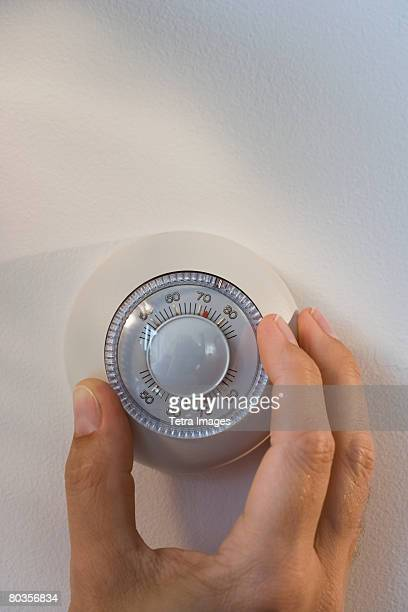 man adjusting thermostat - thermostat stock photos and pictures