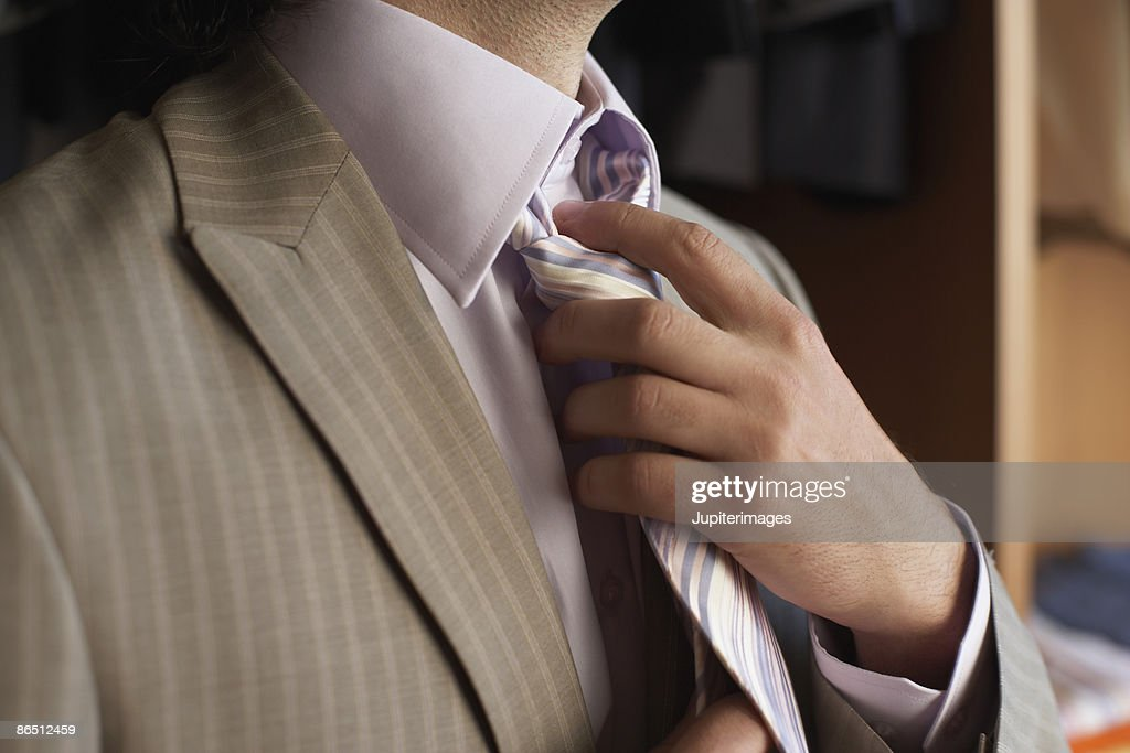 Man adjusting tie : Stock Photo