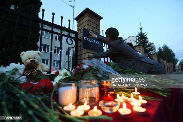 """Man adjusts a board reading """"We mourn"""" at a makeshift memorial for victims of the shooting at School No. 175 in Kazan on May 11, 2021. - At least..."""