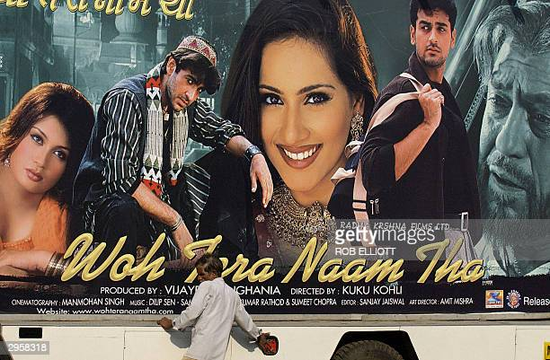 A man adjusts a large poster on the back of a mobile sign truck advertising of one of the latest movies Woh Tera Naam Tha to be released this week in...