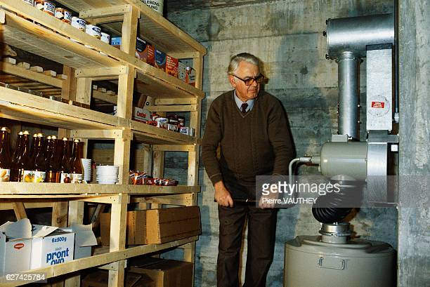 A man adjusts a machine in a fallout shelter in Bern A stockpile of food and supplies lines the shelves next to him stored in case of nuclear war
