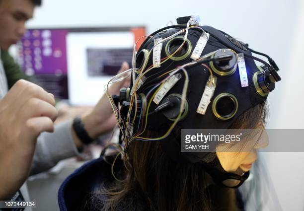 A man adjusts an electroencephalography decoder or emotion decoder from National Central University on display at the 2018 Future Tech Expo in Taipei...
