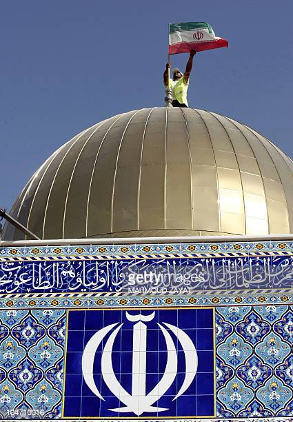A man adjusts an Iranian flag on the dome of a Shiite Muslim mosque in the southern Lebanese town of Marun alRas on October 4 as the town prepares...